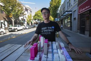 Cory Crocker, a volunteer advocate in the U District, has helped orchestrate a set of recommendations for how people will get around in the neighborhood once the new light-rail station there opens in 2021. He's showing a model of growth expected in the U District. (Steve Ringman / The Seattle Times)