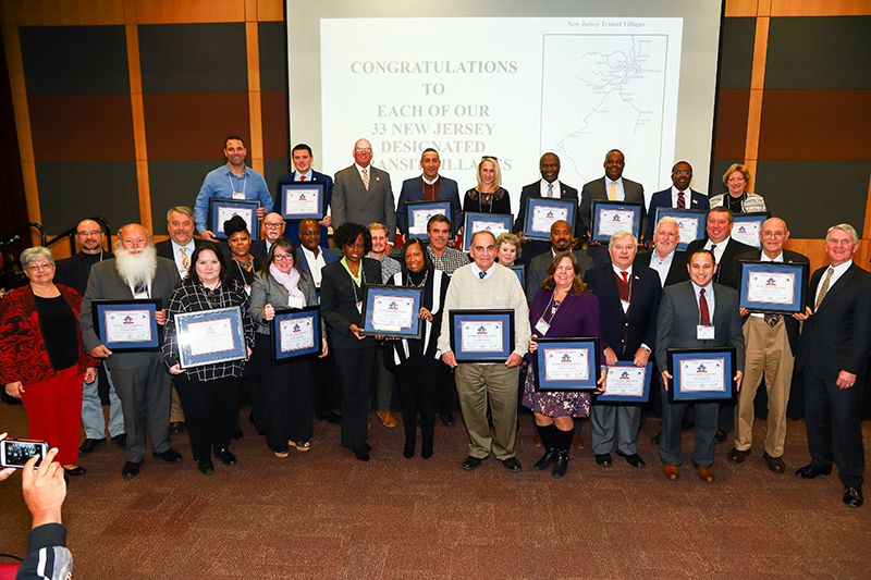 NJDOT Commissioner Diane Gutierrez-Scaccetti (left) and NJ TRANSIT President and CEO Kevin Corbett (right) join representatives from the thirty-three designated New Jersey Transit Village honored at the recent event celebrating 20th anniversary of the New Jersey Transit Village Initiative.
