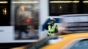A traffic enforcer between a bus and a taxi in NYC captured by Emil Bruckner on Unsplash