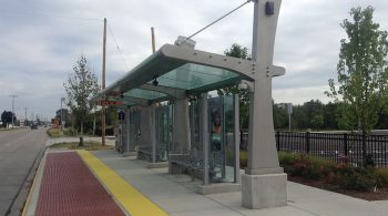 Image of a covered glass and grey bus shelter with a wide curb-level boarding area