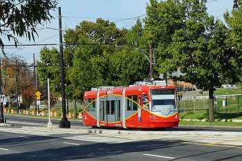 Image of a red streetcar with an empty road and trees in the background. The streetcar's destination reads: Union Station.