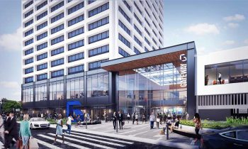 """Rendering of Newark gateway center redevelopment, the white blocky building's base is replaced by a glass, airy atrium with a sign that says """"Gateway"""""""