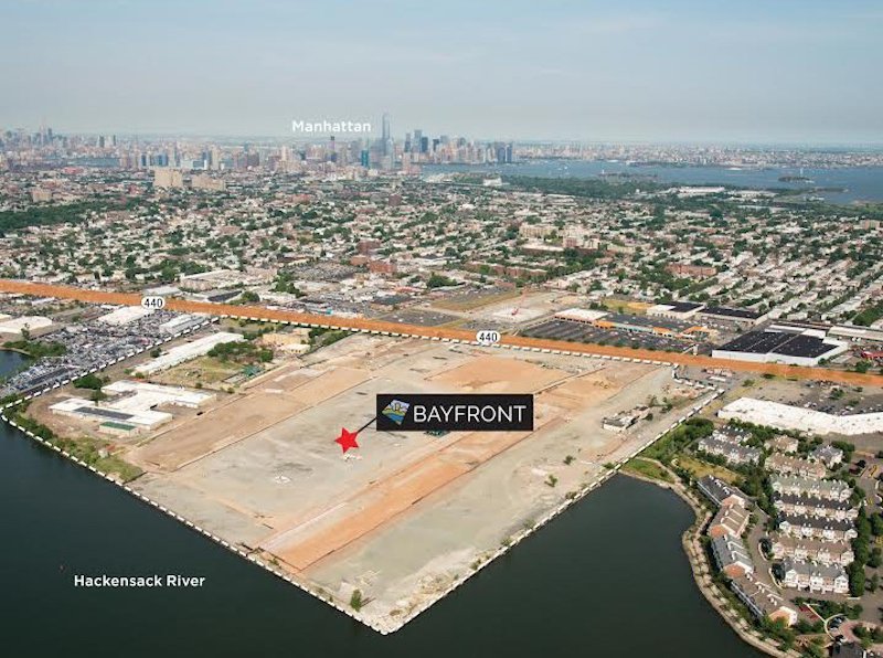 Image of a large, vacant light, with a text label that says Bayfront, in front of it is the Hackensack River, and, behind it, in the distance, is Manhattan.