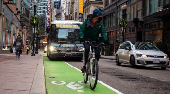Image of a man riding in a bike lane in Boston with a Silver Line 5 Bus to Nubian Square behind him