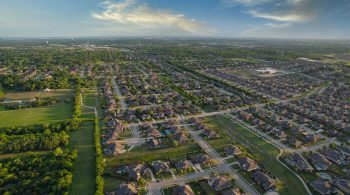 Image of a sprawling suburban development of grey-capped cookie-cutter homes set around cul-de-sacs in Texas