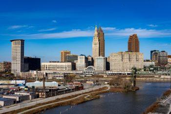 Image of a downtown cityscape with a tall tan arc deco building in the center, with two darker red skyscraper to its right. In the foreground, water flows by an industrial area