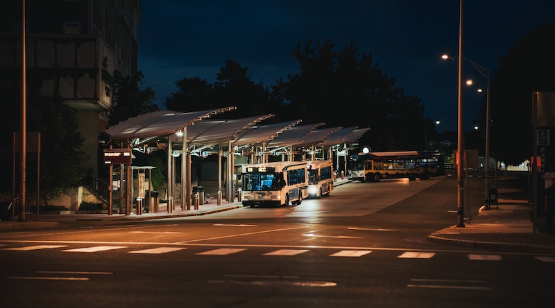 Image of several buses waiting at bus bays at a station at night, to the left is a multistory building.