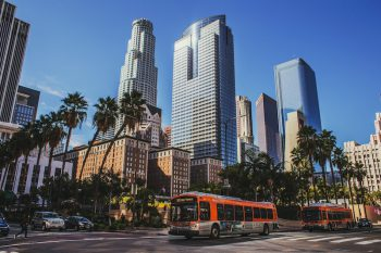 Image of two orange LA Metro buses crossing an intersection, wreathed in palm trees, several skyscrapers loom in the background.