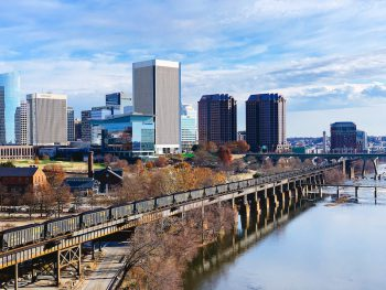 Skyline of Richmond, Virginia, with a CSX coal train rolling along the waterfront, next to a river.