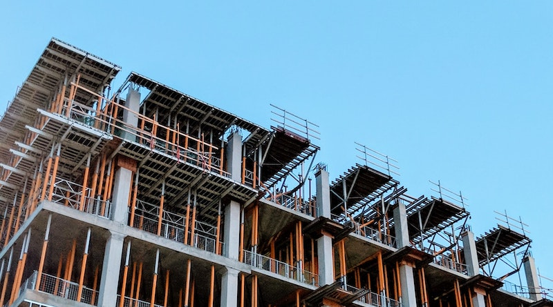 Image of an under construction multistory building with a clear blue sky in the background.
