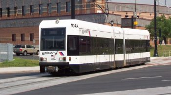 A white, two car light rail car on a street, reading NJ TRANSIT