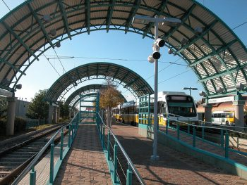 Image of a light rail station, open-air, with a yellow and white DART train pulling into the station