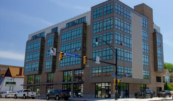 Image of a grey, six story building with ground-floor retail
