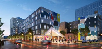 Two blocky, five story residential buildings, grey with multiple colors in shapes painted onto them, at the ground floor is an entrance for an art gallery.