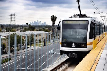 A light rail vehicle reading La Cienaga with a Metro Logo on an elevated platform, with the downtown Los Angeles visible in the background, and a palm tree in the mid-ground.
