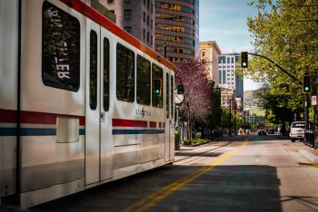 Image of a white light rail car reading UTA Trax going down an urban street with a hill in the background