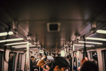 A croded subway car with people standing in the aisle, some holding their hands to the bar, most looking down