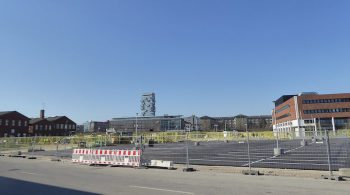 An industrial area with ongoing construction, old red-brick buildings and new ones scattered in between, fencing shows that construction is not yet complete