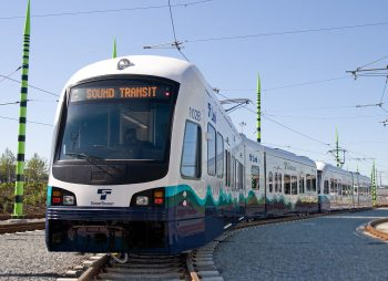 A white light rail vehicle with the front LED display reading Sound Transit