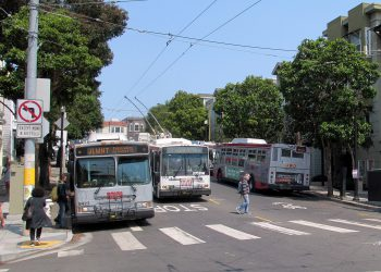 Several buses sit at an intersection, with the Muni logo on their fronts, the one in the middle is connected to wires overhead.