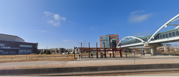 From the perspective of a highway, a BRT station, a pedestrian overpass, and a transit village in the background