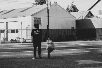 A black and white photo of a woman waiting at a spare bus stop in an industrial area